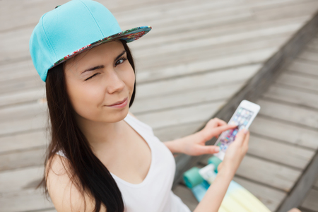 Cute young white brunette girl using big smartphone with wink in her eyes.