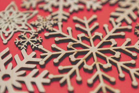 Photo for Handmade wooden snowflakes for Christmas background.Red New Year celebration backdrop with hand made crafts made from eco friendly wood material - Royalty Free Image