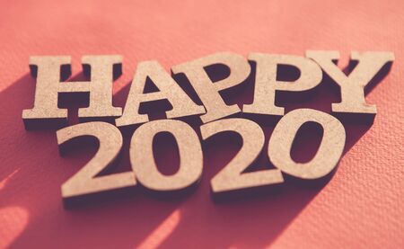 Photo for Happy 2020 background.Red wallpaper with wooden rustic style letters shot on paper backdrop,edited with fading film filter and low contrast.Winter holiday poster  - Royalty Free Image