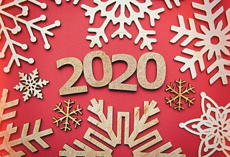 Photo for Red Christmas and New Year 2020 background.Handmade crafts and winter home decor made from eco friendly wood material in flat lay style on paper backdrop - Royalty Free Image