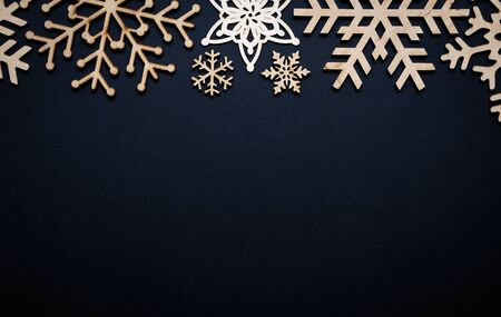 Photo for Winter holiday background.Hand made wooden rustic snowflakes on black paper backdrop for Christmas Eve and Happy New Year poster.Empty space on wallpaper for text - Royalty Free Image