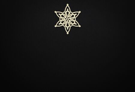 Photo for Christmas & New Year background.Black wallpaper with handmade wooden snowflake in flat lay.Empty space for text on winter holidays poster - Royalty Free Image