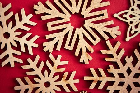 Photo for Beautiful hand made decor for Christmas and Happy New Year celebration.Handmade crafts and home decor for winter holiday.December holidays red background and rustic wooden snowflakes in close up - Royalty Free Image
