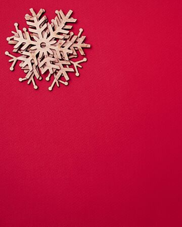 Photo for Red Christmas background.Flat lay snowflakes made from eco friendly wood material for winter holidays home decor.Happy New Year poster template with empty space for invitation text below - Royalty Free Image