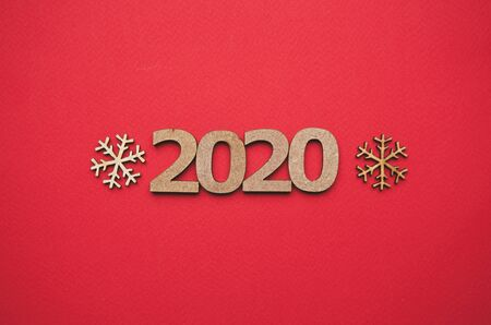 Photo for Red Christmas background with 2020 figures and wooden snow flakes shot from above in flat lay style.Handmade crafts for winter holiday celebration.Hand made decor for wallpaper - Royalty Free Image