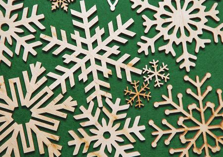 Photo for Wooden snowflakes in flat lay on green background.Christmas toys made from rustic wood material.New Year decorations in flat layout for wallpaper design.Handmade crafts for winter holidays home decor - Royalty Free Image