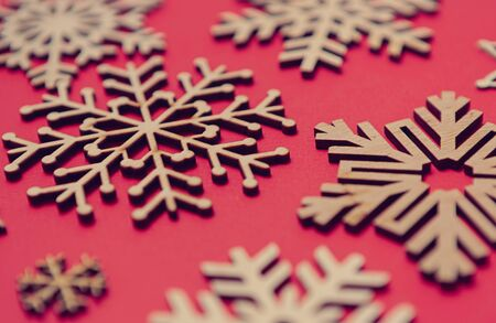 Photo for Rustic wooden snowflakes on red Christmas background.Handmade crafts made from eco friendly wood.New Year toys for home decor in close up - Royalty Free Image