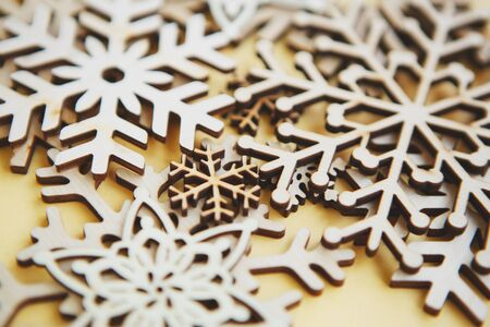 Photo for Wooden snowflakes for Christmas & New Year background.Beautiful hand made crafts for winter holidays decoration.Handmade home decor on yellow backdrop.Beautiful rustic snow flake made from wood - Royalty Free Image