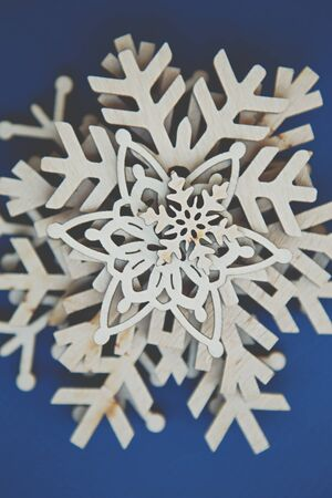 Photo for Beautiful handmade wooden snowflakes in flat lay on blue background.Hand made crafts for home decor on winter holidays,shot from above - Royalty Free Image