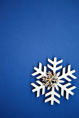 Photo for Blue winter holiday background in flat lay style.Handmade wooden snowflakes shot from above on empty backdrop.Vertical poster template for Christmas & Happy New Year celebration party.Hand made crafts - Royalty Free Image