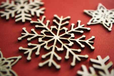 Photo for Handmade Christmas snowflake toy on red background.Hand made wooden crafts for home decoration in winter holiday season.Rustic snowflakes for New Year decorations,edited with vintage style film filter - Royalty Free Image