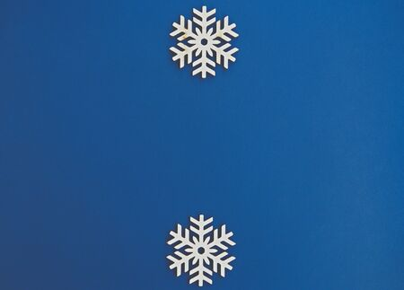 Photo for Blue winter holiday background.Flat lay wooden snowflakes on empty backdrop for Merry Christmas & Happy New Year wallpaper design.Place text on empty space for holidays poster - Royalty Free Image