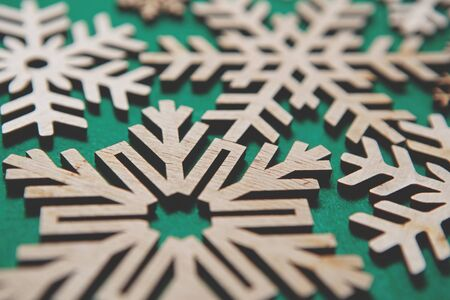 Photo for Handmade wooden Christmas snowflakes on green background.Beautiful snow flake figures made from natural eco friendly wood material for winter holidays home decor.Ecological decorations for New Year - Royalty Free Image