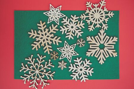 Photo for Handmade wooden snowflakes in flat lay on Christmas themed background.Red & green backdrop with hand made crafts for winter holidays.New Year home decor made from ecological  wood material - Royalty Free Image