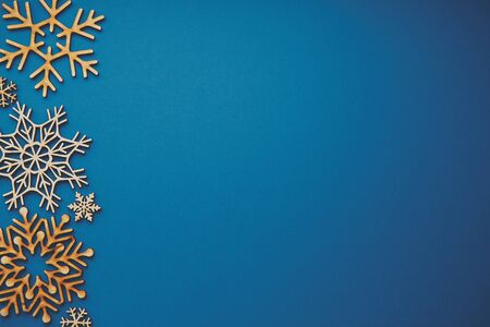 Photo for Flat lay Christmas background with copy space.Blue New year backdrop with handmade wooden snoflakes shot from above in flat layout style.Empty space for text on wallpaper template - Royalty Free Image