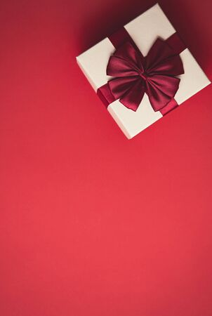 Photo for Flat lay red Christmas background with gift box shot from above.Decorative white present package with red ribbon for winter holidays.New Year presents and gift card template with empty space for text - Royalty Free Image