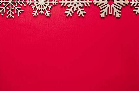 Photo for Red Christmas background.Flat lay backdrop with handmade wooden snowflakes on paper backdrop.Empty space for text on New Year poster template.Winter holidays wallpaper with minimalistic design - Royalty Free Image