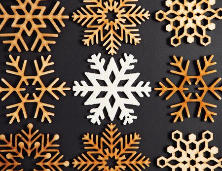 Photo for Flat lay black Christmas background.Wooden decorative snowflakes shot directly from above.New Year celebration party poster template with rustic toys made from wood.Dark winter holidays wallpaper - Royalty Free Image