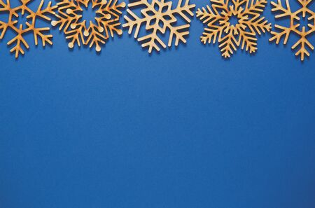 Photo for Flat lay Christmas background.Blue poster template with empty space for text.Winter holiday wallpaper with handmade wooden snowflakes.New Year celebration postcard in rustic design - Royalty Free Image