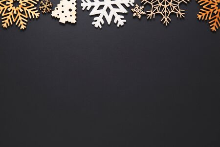 Photo for Flat lay Christmas background.Handmade New Year decorations on black poster with empty space for text.Winter holiday postcard template in flat layout style.Rustic wooden snowflakes on wallpaper - Royalty Free Image