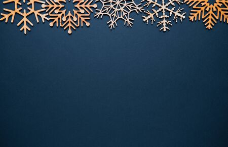 Photo for Blue Christmas background.Flat lay poster with handmade wooden snowflakes.Rustic style decoration on empty wallpaper template.Beautiful hand crafted snowflake toys in flay layout for New Year postcard - Royalty Free Image
