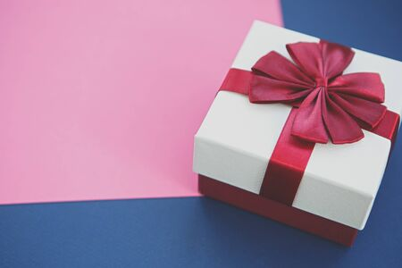 Photo for White Christmas present box with red ribbon on pink & blue paper backgrounds.Decorative New Year gift box in close up - Royalty Free Image