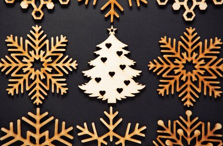 Photo for Flat lay wooden Christmas tree toy on black background.Rustic handmade decorations shot from above.Beautiful hand crafted decor elements for winter holidays - Royalty Free Image