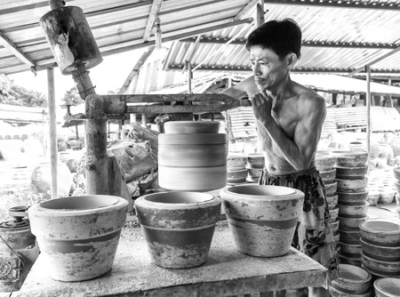 Binh Duong, Vietnam - October 25th, 2015: The potter is cleverly molded plastic flower pot spinning with concentration for work in the morning in the village of Binh Duong, Vietnam