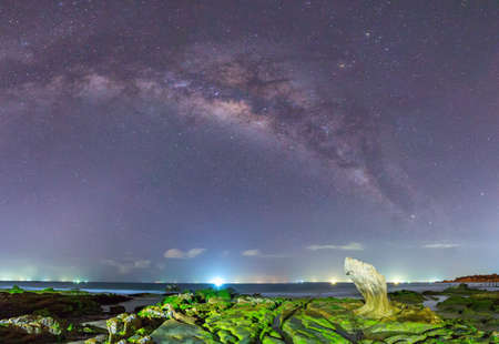 Overview Milky Way ancient moss fossil inside the reef at night with the bright constellation formed long colorful streaks, below the moss-covered rocks on the beach while enjoying beautiful galaxy in the night