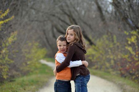 a crabby boy and his sister hug on an autumn day
