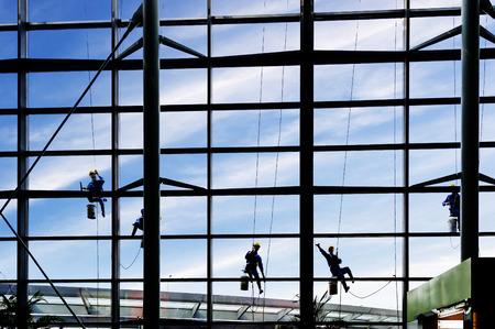 Washers wash the windows of modern skyscraper