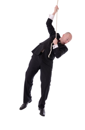 Businessman hanging onto a rope fearing from below isolated on white