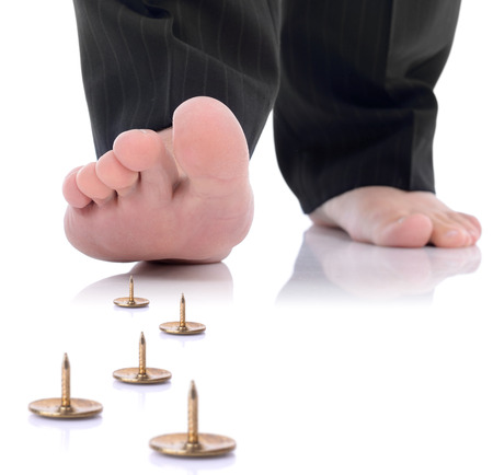 concept of unforseen problem or danger ahead, foot stepping on a pin isolated on a white background