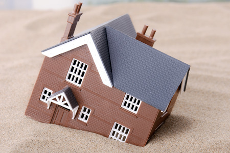 A house sinking in sand, concept for housing problems