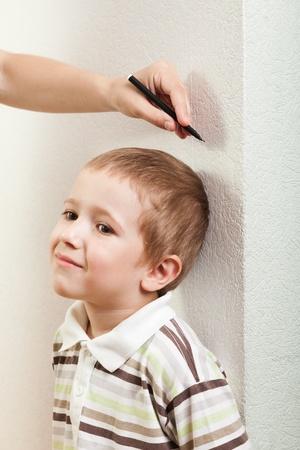Human hand measure little child boy height growth