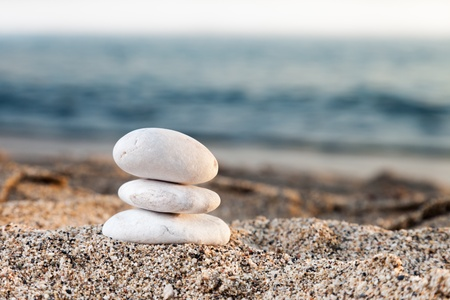 Stability and harmony - stack or pile of balancing rock stones on summer vacations sea sun b