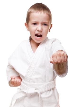 Martial art sport - child boy in white kimono training karate punch