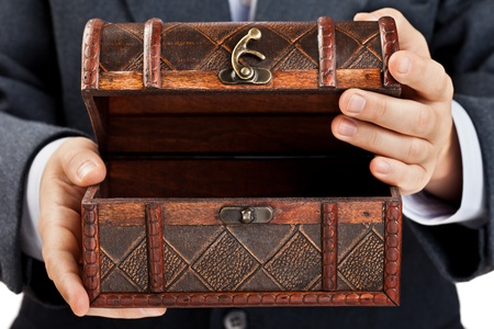 Business man hand holding old antique brown wood treasure chest or box white isolated