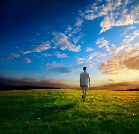 Foto de one man and field of spring grass and sunset - Imagen libre de derechos