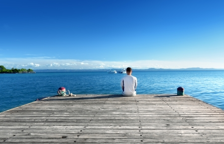 young man relax siting on pier の写真素材