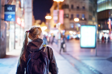 Photo pour Back view of girl walking on city street at night, Prague - image libre de droit