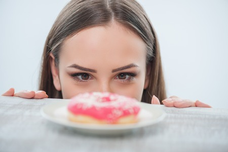 Beautiful girl is looking at unhealthy donut with appetite on a table. Isolated on a white background