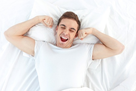 Cheerful young man is waking up after sleeping in the morning. He is yawing and stretching his arms up. His eyes are closed with relaxation. He is lying in the bed