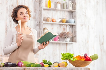 Cheerful young woman is cooking in the kitchen with joy. She is standing and holding a book of recipe. The lady is touching a wood spoon to her face and dreaming. She is smilingの写真素材