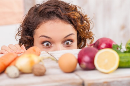 Close up of head of cheerful young woman looking at the vegetables with appetite. She is peeping through the table with temptation