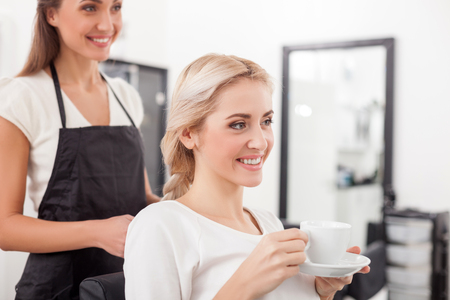 Cheerful young hairdresser is braiding female hair. She is standing in apron at beauty salon. The woman is sitting and drinking tea. They are smiling happilyの写真素材