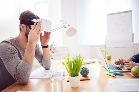 Cheerful young office worker is watching a virtual reality device with interest. He is sitting at the desk. His colleague is typing on laptop