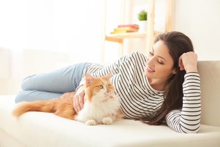Beautiful young woman is resting with her small friend. She is lying on sofa and stroking a cat. The lady is smiling happily