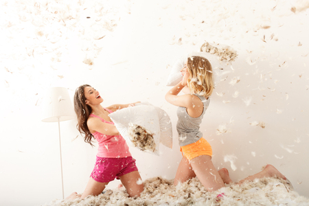 Happy girls fighting with pillows in pajamas. They are kneeling on bed and smiling. Feathers around them