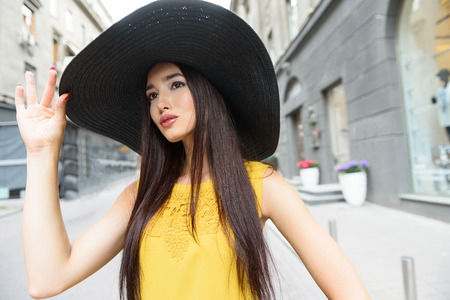 Stylish young woman is having walk in city. She is looking forward with interest. Lady is standing and touching hat elegantly
